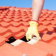 Roof repair, worker with yellow gloves replacing red tiles